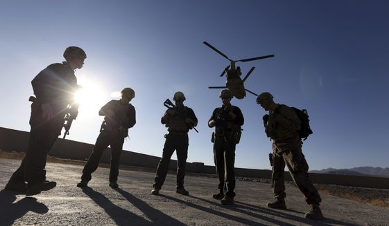 In this Nov. 30, 2017, file photo, American soldiers wait on the tarmac in Logar province, Afghanistan. With American troops withdrawing from Afghanistan, pressure has been mounting for the Biden administration to plan a military evacuation of Afghans who supported U.S. military operations during two decades of war in their country. (AP Photo/Rahmat Gul, File)