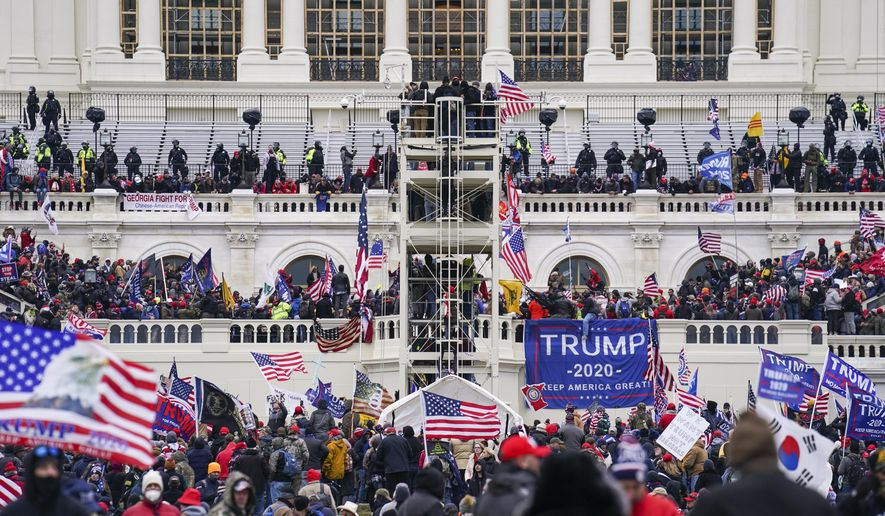 In this Jan. 6, 2021, file photo insurrectionists loyal to President Donald Trump breach the Capitol in Washington. Prosecutors secured the first guilty plea in the major case brought against members of the Oath Keepers extremist group in the attack on the U.S. Capitol, while an Indiana woman who became first person to be sentenced for the Jan. 6 riot avoided time behind bars.  (AP Photo/John Minchillo)