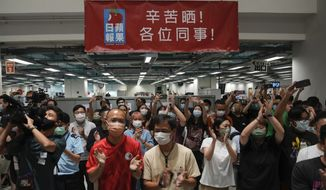 Staff members gather at the Apple Daily headquarters in Hong Kong, Wednesday, June 23, 2021. Hong Kong's pro-democracy Apple Daily newspaper will stop publishing Thursday, following last week's arrest of five editors and executives and the freezing of $2.3 million in assets under the city's one-year-old national security law. (AP Photo/Kin Cheung)