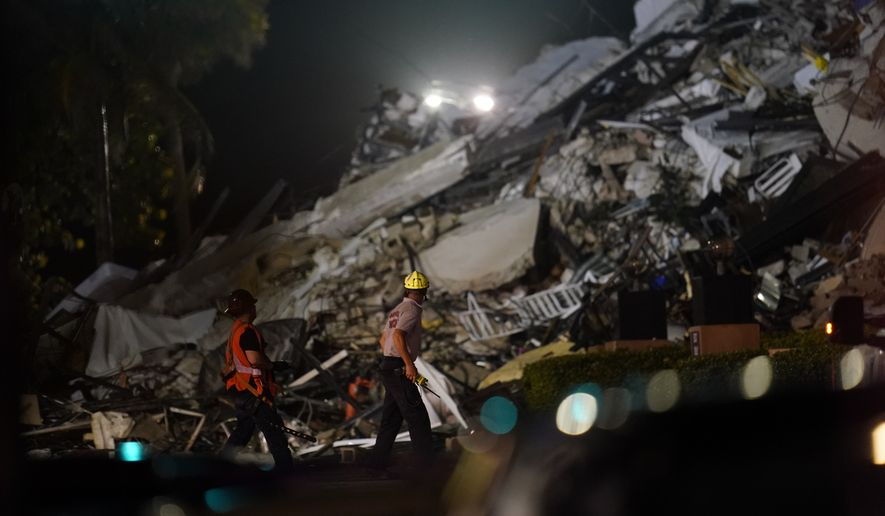 Rescue workers walk beside the rubble as rescue efforts continue where a wing of a 12-story beachfront condo building collapsed, Thursday, June 24, 2021, in the Surfside area of Miami.(AP Photo/Gerald Herbert)