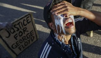 """In this May 29, 2020, photo, a protester reacts after being pepper-sprayed by police and receiving a sodium bicarbonate mixture from fellow demonstrators to help neutralize the effect, in St. Paul, Minn. Former Minneapolis police Officer Derek Chauvin faces decades in prison when he is sentenced Friday for murder in the May 2020 death of George Floyd. Floyd's death, filmed by a teenage bystander as Chauvin pinned Floyd to the pavement for about 9 and a half minutes and ignored Floyd's """"I can't breathe"""" cries until he eventually grew still, reignited a movement against racial injustice that swiftly spread around the world and continues to reverberate.(AP Photo/John Minchillo) **FILE**"""