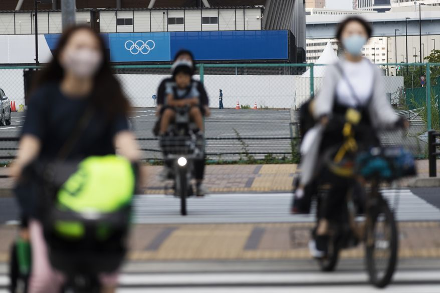 Women carry their children on their bicycles as they ride through an intersection near a sporting arena planned to be used during the Tokyo 2020 Olympic and Paralympic Games in Tokyo Thursday, June 24, 2021. (AP Photo/Hiro Komae)