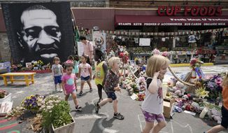 Preschool children visit the site where George Floyd was murdered by then-Minneapolis Police Officer Derek Chauvin, as the kids took a field trip to the memorial, Thursday, June 24, 2021, in Minneapolis. Chauvin is scheduled to be sentenced on Friday. (AP Photo/Julio Cortez)