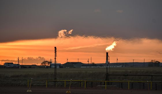 In this Tuesday, May 18, 2021, file photo, flares burn natural gas from oil production in the Fort Berthold Indian Reservation east of New Town, North Dakota. Oil pumped from Native American lands in the U.S. increased about tenfold since 2009 to more than 130 million barrels annually, bringing new wealth to a small number of tribes. Tribes left out of the drilling boom have become increasingly outspoken against fossil fuels as climate change's impacts grow worse. (AP Photo/Matthew Brown)