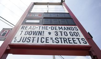 A sign is seen on a gas station's marquee near the site where George Floyd was killed by then Minneapolis Police officer Derek Chauvin, Thursday, June 24, 2021, in Minneapolis. Chauvin is scheduled to be sentenced Friday. (AP Photo/Julio Cortez)