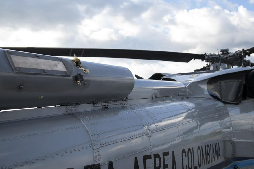 In this photo released by Colombia's Presidency, bullet holes are seen on the fuselage of a Colombian Air Force helicopter that was fired upon while Colombia's President Ivan Duque and members of his Cabinet were traveling on the helicopter, at the airport in Cucuta, Colombia, Friday, June 25, 2021. Duque said the aircraft was attacked while traveling on it with his ministers of defense and interior in the Catatumbo region, on the northeastern border with Venezuela. (Cesar Carrion/Presidency of Colombia via AP)