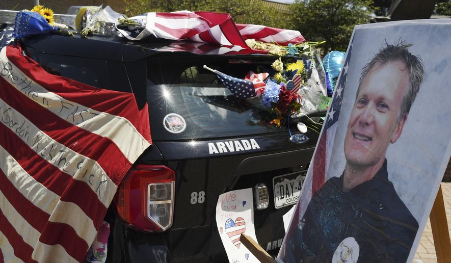 Flowers, flags and notes cover a patrol car and bike outside Arvada City Hall during a memorial for Arvada Police Officer Gordon Beesley on Tuesday, June 22, 2021 in Arvada, Colo. Officer Beesley was killed during a shooting in Olde Town Arvada. (RJ Sangosti/The Denver Post via AP)