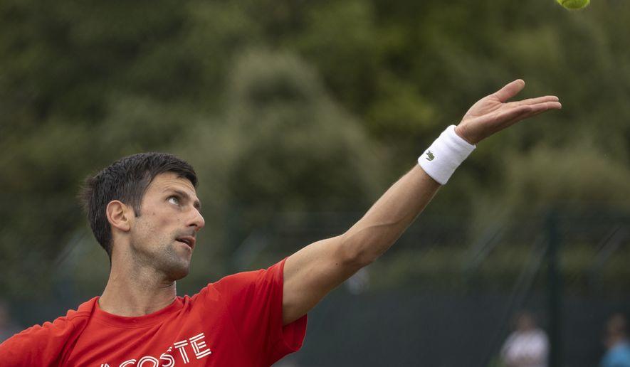 Serbia'a Novak Djokovic serves, during his practice match, prior to the Wimbledon Tennis Championships in London, Saturday June 26, 2021. (David Gray/Pool via AP) **FILE**
