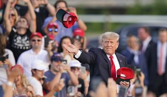 """Former President Donald Trump throws 'Save America"""" hats to the audience before speaking at a rally at the Lorain County Fairgrounds, Saturday, June 26, 2021, in Wellington, Ohio. (AP Photo/Tony Dejak)"""