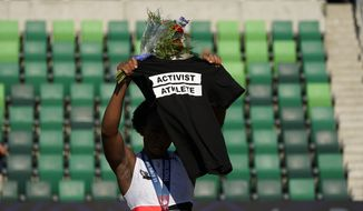 Gwendolyn Berry her Activist Athlete T-Shirt over her head during the metal ceremony after the finals of the women's hammer throw at the U.S. Olympic Track and Field Trials Saturday, June 26, 2021, in Eugene, Ore. Berry finished third. (AP Photo/Charlie Riedel)