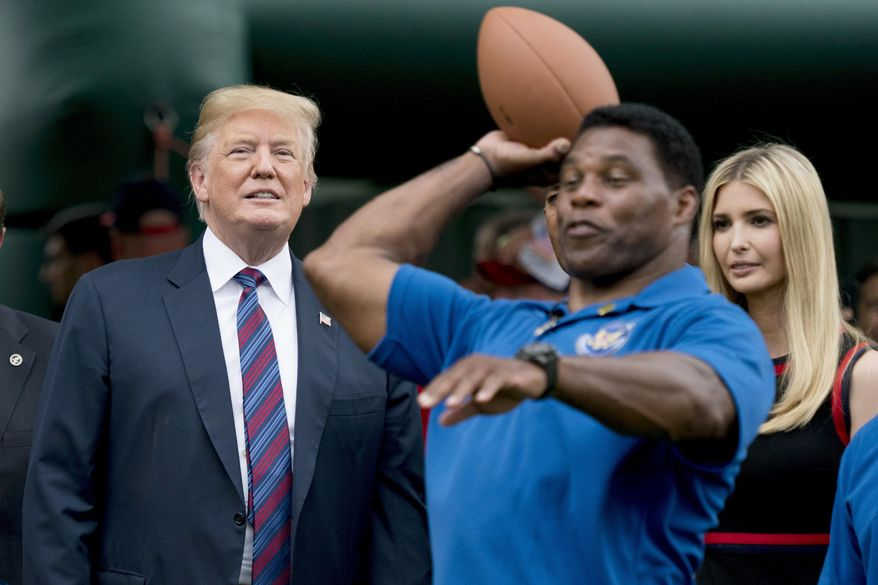 In this May 29, 2018, file photo, President Donald Trump, left, and his daughter Ivanka Trump, right, watch as former football player Herschel Walker, center, throws football's during White House Sports and Fitness Day on the South Lawn of the White House in Washington. The U.S. Senate nomination in a premier battleground like Georgia should be a plum political prize, but a year before Republican voters choose a nominee for the 2022 midterms, they have no clear options. The wildcard is whether football hero Herschel Walker runs and brings the endorsement of former President Donald Trump. (AP Photo/Andrew Harnik)