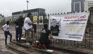 Family of Ricardo Valdes, who disappeared on the road on May 25,   put up posters with their photography during a protest in Monterrey, Nuevo Leon state, Mexico, Thursday, June 24, 2021. As many as 50 people in Mexico are missing after they set off on simple highway trips between the industrial hub of Monterrey and the border city of Nuevo Laredo; relatives say they simply disappeared on the heavily traveled road, which has been dubbed 'the highway of death,' never to be seen again. (AP Photo/Roberto Martinez)