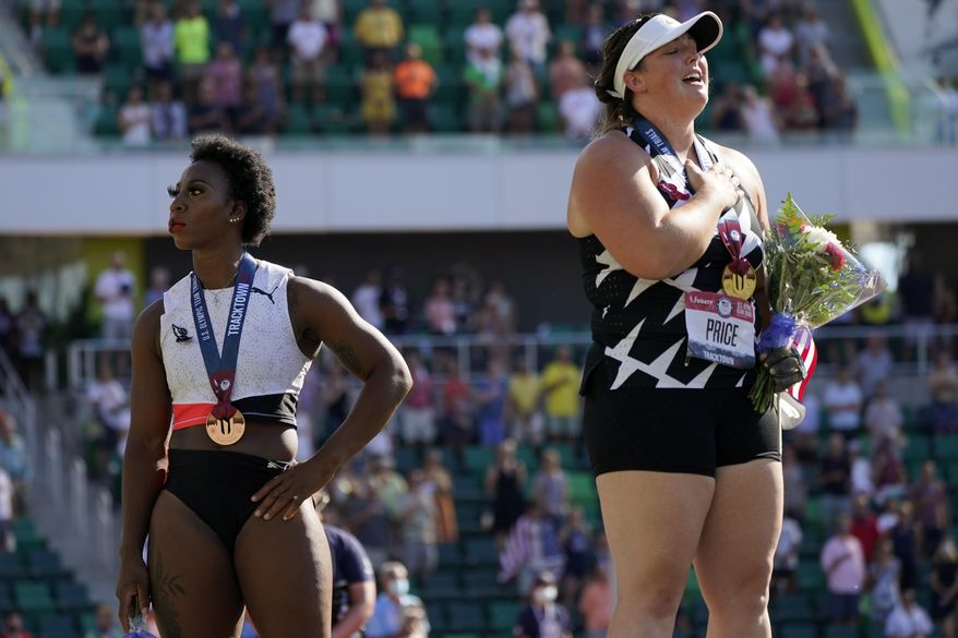 Gwendolyn Berry, left, looks away as DeAnna Price stands for the national anthem after the finals of the women's hammer throw at the U.S. Olympic Track and Field Trials Saturday, June 26, 2021, in Eugene, Ore. Price won and Berry finished third. (AP Photo/Charlie Riedel)