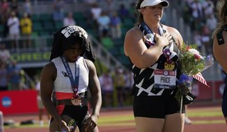 """Gwendolyn Berry, left, drapes her """"Activist Athlete"""" T-Shirt over her head as DeAnna Price stands for the national anthem after the finals of the women's hammer throw at the U.S. Olympic Track and Field Trials Saturday, June 26, 2021, in Eugene, Ore. Price won and Berry finished third. (AP Photo/Charlie Riedel)"""
