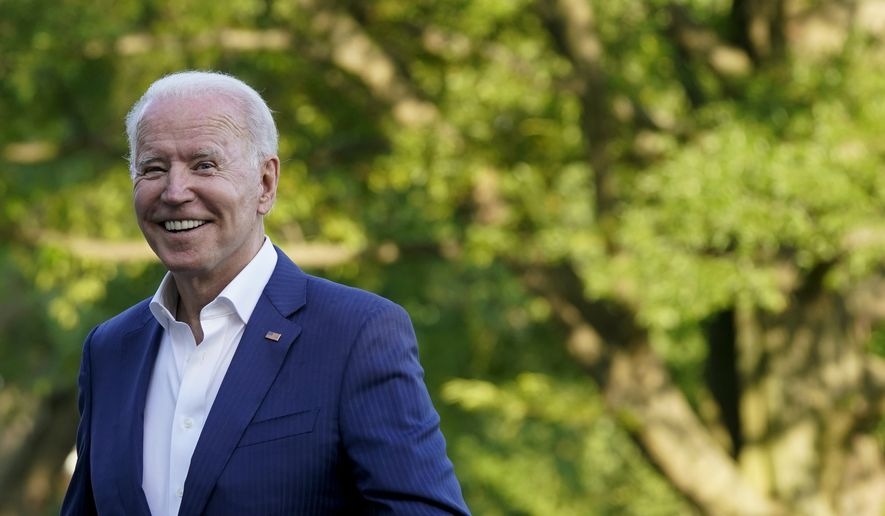 President Joe Biden smiles as he walks on the South Lawn of the White House after stepping off Marine One, Sunday, June 27, 2021, in Washington. (AP Photo/Patrick Semansky)