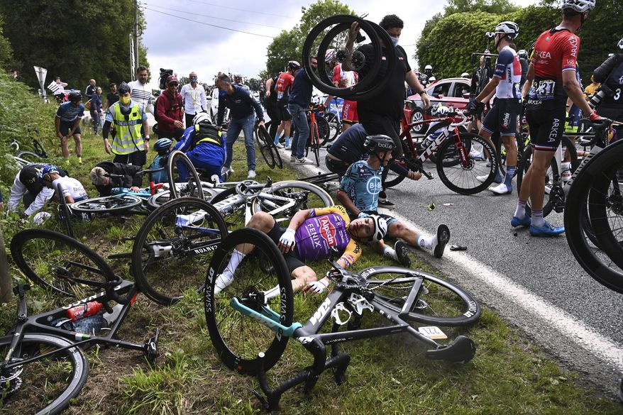 Italy's Kristian Sbaragli, left, and France's Bryan Coquard, right, lie on the ground after crashing during the first stage of the Tour de France cycling race over 197.8 kilometers (122.9 miles) with start in Brest and finish in Landerneau, France, Saturday, June 26, 2021. (Anne-Christine Poujoulat, Pool Photo via AP) **FILE**