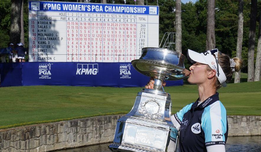 Nelly Korda of the U.S. kisses the trophy after winning the KPMG Women's PGA Championship golf tournament, Sunday, June 27, 2021, in Johns Creek, Ga. (AP Photo/John Bazemore)