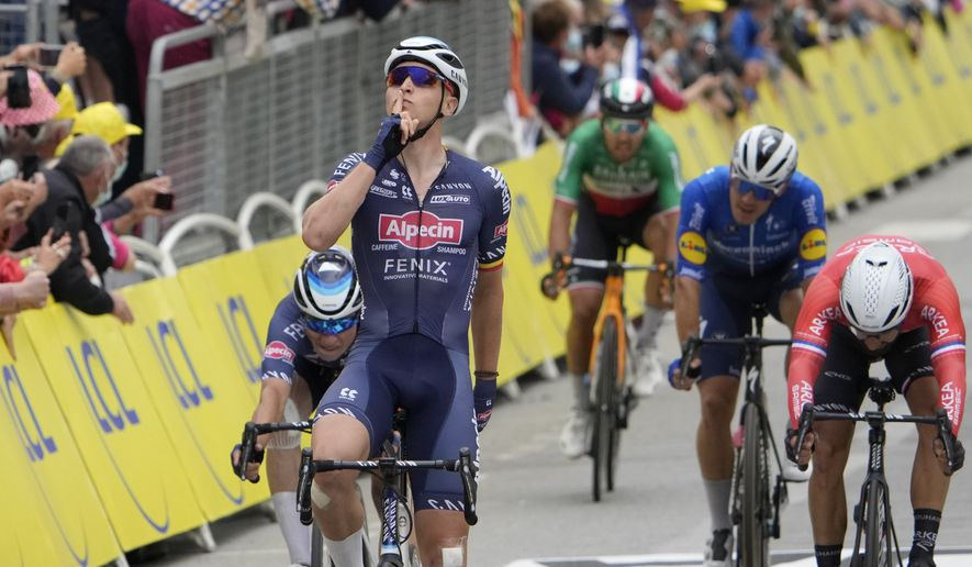 Belgium's Tim Merlier celebrates as he crosses the finish line to win the third stage of the Tour de France cycling race over 182.9 kilometers (113.65 miles) with start in Lorient and finish in Pontivy, France, Monday, June 28, 2021. (AP Photo/Christophe Ena, Pool)