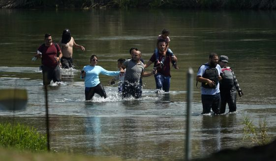 A group of migrants mainly from Venezuela wade through the Rio Grande as they cross the U.S.-Mexico border, Wednesday, June 16, 2021, in Del Rio, Texas. (AP Photo/Eric Gay) ** FILE **