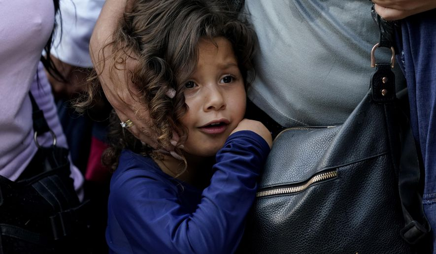 A young migrant girl from Venezuela stands with her mother as they wait with Border Patrol after turning themselves in after crossing the U.S.-Mexico border, Tuesday, June 15, 2021, in Del Rio, Texas. Record numbers of Venezuelans are crossing the U.S.-Mexico border as overall migration swells. They're fleeing turmoil in the country with the world's largest oil reserves and pandemic-induced pain across South America. (AP Photo/Eric Gay)