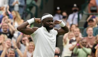 Frances Tiafoe of the US celebrates after winning the men's singles match against Stefanos Tsitsipas of Greece on day one of the Wimbledon Tennis Championships in London, Monday June 28, 2021. (AP Photo/Alastair Grant)
