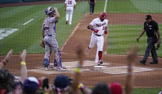 Washington Nationals' Kyle Schwarber, center, crosses home plate for his solo home run during the first inning of a baseball game against the New York Mets at Nationals Park, Monday, June 28, 2021, in Washington. (AP Photo/Alex Brandon)