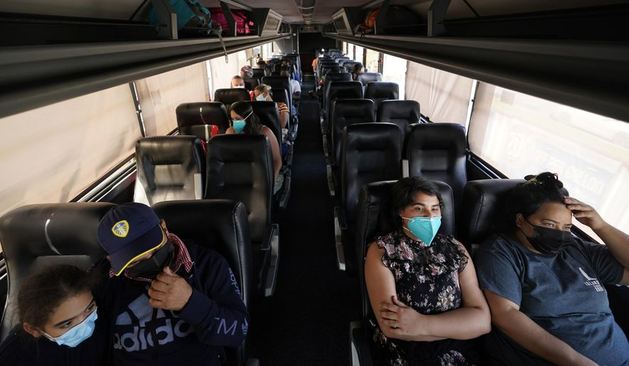 Migrants who entered the United States illegally and turned themselves sit on a bus after they were processed by U.S. Customs and Border Patrol, Monday, June 14, 2021, in Del Rio, Texas. Record numbers of Venezuelans are crossing the U.S.-Mexico border as overall migration swells. Unlike the farmers and low-wage workers who come from Mexico or Central America, the Venezuelans include bankers, doctors and engineers. (AP Photo/Eric Gay)