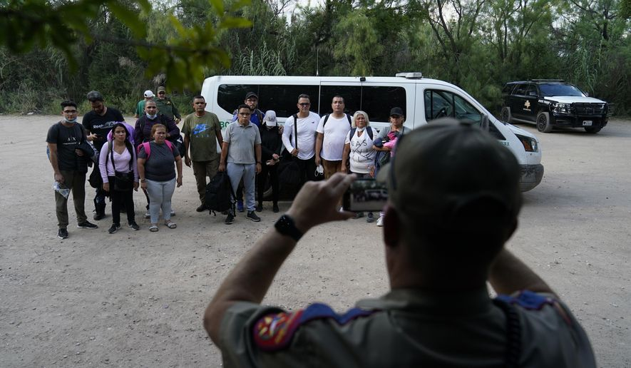 A group of migrants, mostly from Venezuela are photographed after turning themselves in after crossing the U.S.-Mexico border, Tuesday, June 15, 2021, in Del Rio, Texas. Many of the migrants cross during daylight, looking to turn themselves in to Border Patrol agents who document their arrival. (AP Photo/Eric Gay)