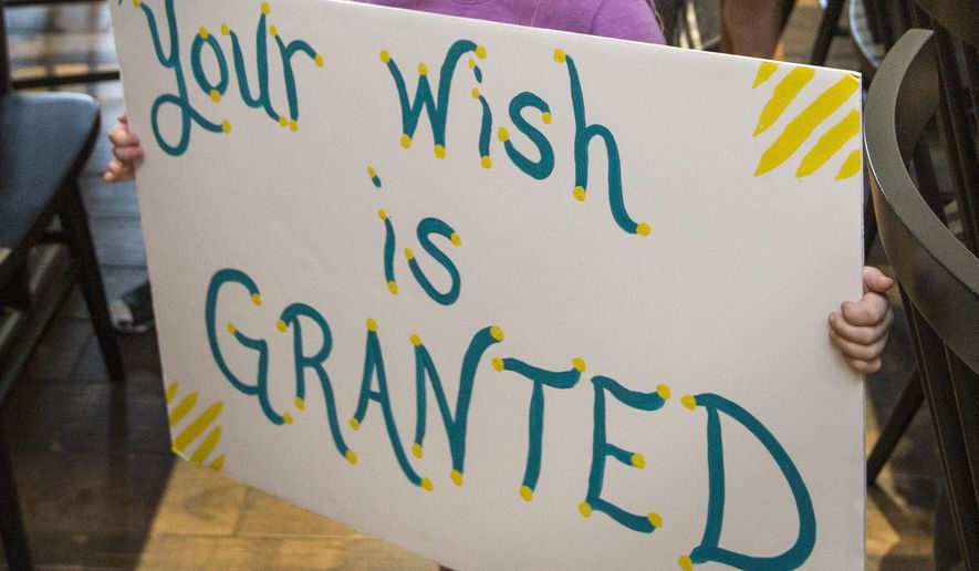 """In this Thursday, Aug. 22, 2019, file photo, a girl holds a sign while waiting for her cousin to arrive for a surprise Make-A-Wish announcement in Rogers, Ark. In June 2021, the Make-a-Wish Foundation is disputing what it calls a """"misinformation"""" campaign about whether children who aren't vaccinated against COVID-19 will be eligible to have their wishes granted. (Ben Goff/The Northwest Arkansas Democrat-Gazette via AP) ** FILE **"""