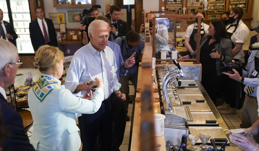 President Joe Biden hands ice cream to Sen. Tammy Baldwin, D-Wis., as Wisconsin Gov. Tony Evers, left, watches, during a stop at The Pearl Ice Cream Parlor Tuesday, June 29, 2021, in La Crosse, Wis. (AP Photo/Evan Vucci)