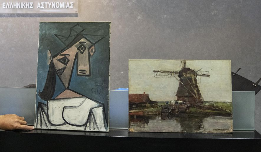 A cubist female bust by the Spanish painter Picasso, left, and a 1905 representational oil painting of a riverside windmill by the Dutch painter Mondrian are displayed by police officers, in Athens during a press conference, on Tuesday, June 29, 2021. Greek police says they have recovered two paintings by 20th century masters Pablo Picasso and Piet Mondrian, nearly a decade after their theft from the country's biggest state art gallery in Athens. (AP Photo/Petros Giannakouris)