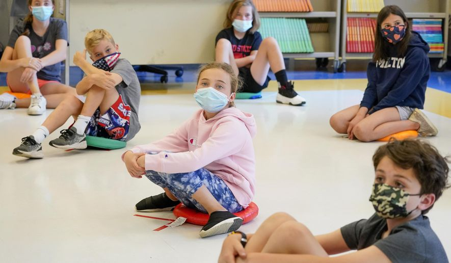 In this May 18, 2021 file photo, fifth graders wearing face masks are seated at proper social distancing during a music class at the Milton Elementary School in Rye, N.Y. (AP Photo/Mary Altaffer, File) ** FILE **