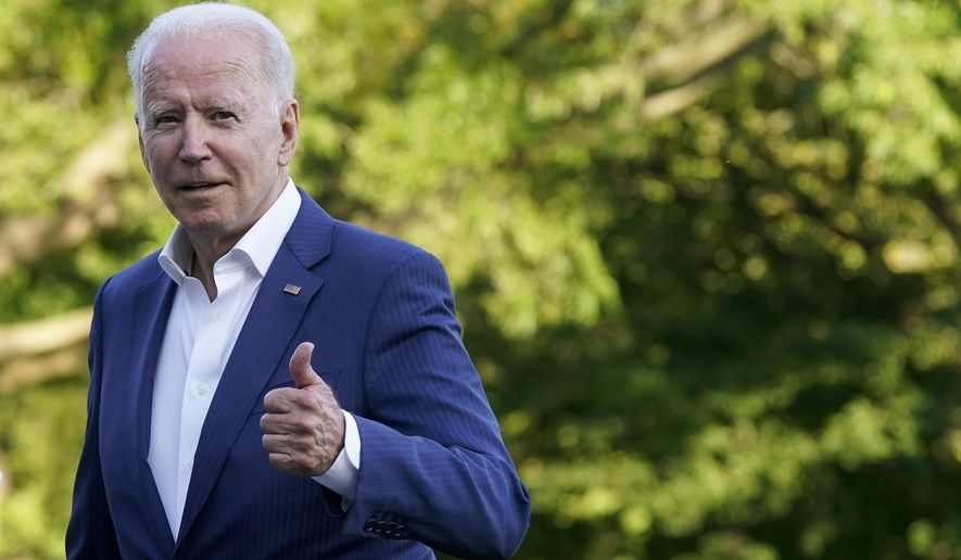 President Joe Biden gestures as he walks on the South Lawn of the White House after stepping off Marine One, on Sunday. (AP Photo/Patrick Semansky)