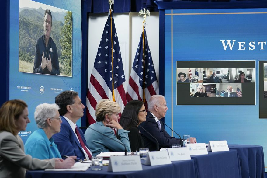 President Joe Biden, right, listens as California Gov. Gavin Newsom, on screen, speaks during an event in the South Court Auditorium on the White House complex in Washington, Wednesday, June 30, 2021, with cabinet officials and governors from Western states to discuss drought and wildfires. Others a the table are, from left, Deputy Secretary of Defense Kathleen Hicks, National Climate Adviser Gina McCarthy, White House chief of staff Ron Klain, Energy Secretary Jennifer Granholm and Interior Secretary Deb Haaland. (AP Photo/Susan Walsh)