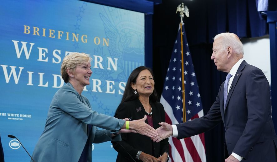 President Joe Biden, right, greets Energy Secretary Jennifer Granholm, left, and Interior Secretary Deb Haaland, center, before the start of an event in the South Court Auditorium on the White House complex in Washington, Wednesday, June 30, 2021, with Cabinet officials and governors from Western states to discuss drought and wildfires. (AP Photo/Susan Walsh)
