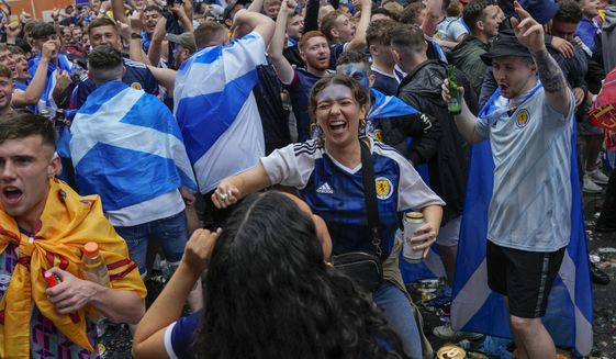 In this Friday, June 18, 2021, photo Scotland fans gather in Leicester Square prior to the Euro 2020 soccer championship group D match between England and Scotland, in London. Scottish authorities have reported nearly 2,000 coronavirus cases linked to watching European Championship games in stadiums, public gatherings, pubs or private homes. Public Health Scotland says 1,294 of the people infected had traveled to London for the England game on June 18. But it says only 397 of them were at Wembley Stadium for the match. (AP Photo/Kirsty Wigglesworth) **FILE**