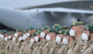 Soldiers of the German Armed Forces have lined up in front of the Airbus A400M transport aircraft of the German Air Force for the final roll call in Wunstorf, Germany, Wednesday, June 30, 2021. The last soldiers of the German Afghanistan mission have arrived at the air base in Lower Saxony. The mission had ended the previous evening after almost 20 years. The soldiers had been flown out with four military planes from the field camp in Masar-i-Sharif in the north of Afghanistan. (Hauke-Christian Dittrich/Pool via AP)