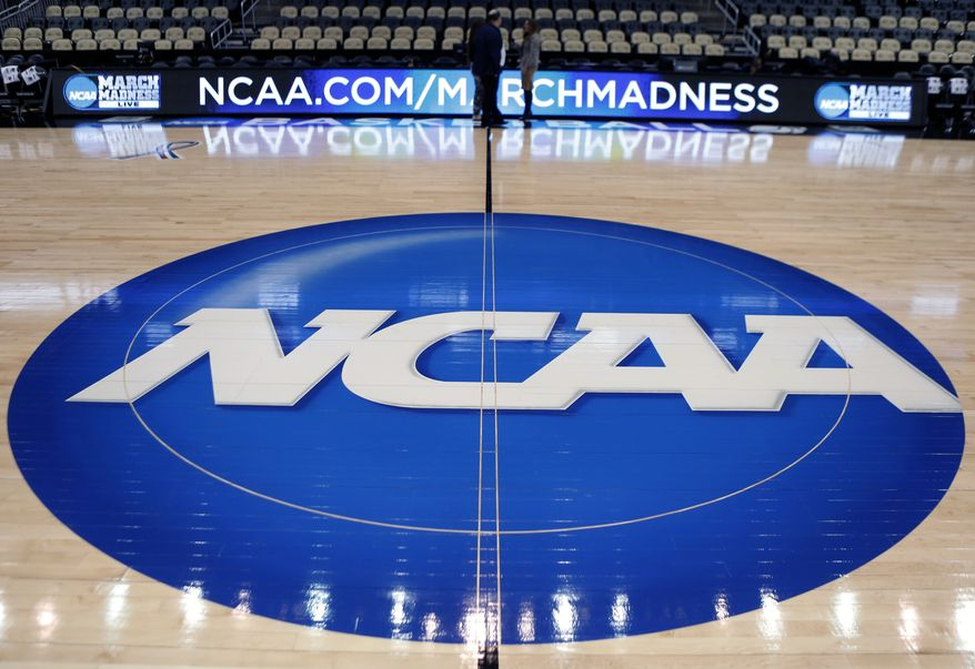 In this March 18, 2015, file photo, the NCAA logo is displayed at center court as work continues at The Consol Energy Center in Pittsburgh, for the NCAA college basketball tournament. The NCAA Board of Directors is expected to greenlight one of the biggest changes in the history of college athletics when it clears the way for athletes to start earning money based on their fame and celebrity without fear of endangering their eligibility or putting their school in jeopardy of violating amateurism rules that have stood for decades. (AP Photo/Keith Srakocic, File)