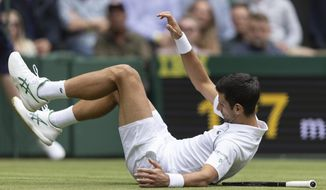 Novak Djokovic of Serbia falls whilst playing against South Africa's Kevin Anderson during the men's singles second round match on day three of the Wimbledon Tennis Championships in London, Wednesday June 30, 2021. (Ian Walton/Pool via AP)
