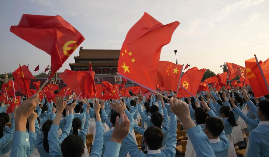 Chinese flags are waved during a rehearsal for a ceremony to mark the 100th anniversary of the founding of the ruling Chinese Communist Party at Tiananmen Gate in Beijing Thursday, July 1, 2021. (AP Photo/Ng Han Guan)