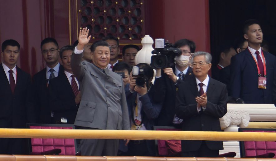 Chinese President Xi Jinping, center, waves next to former President Hu Jintao, right, during a ceremony to mark the 100th anniversary of the founding of the ruling Chinese Communist Party at Tiananmen Gate in Beijing Thursday, July 1, 2021. (AP Photo/Ng Han Guan) ** FILE **