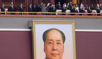 Chinese President Xi Jinping, center, waves above a large portrait of the late leader Mao Zedong during a ceremony to mark the 100th anniversary of the founding of the ruling Chinese Communist Party at Tiananmen Gate in Beijing Thursday, July 1, 2021. (AP Photo/Ng Han Guan)