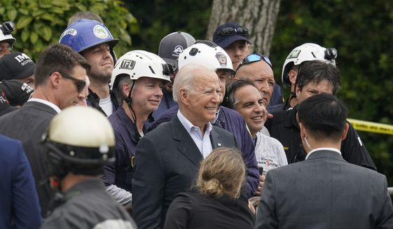 """U.S. President Joe Biden, center, poses for a photo with search and rescue workers after visiting a makeshift memorial to the scores of victims of the partial collapse at the Champlain Towers South condo building, Thursday, July 1, 2021, in Surfside, Fla. President Biden drew on his own experiences with grief and loss to comfort families affected by the Florida condo collapse, telling them to """"never give up hope"""" even as the search for survivors paused early Thursday, a week after the building came down.(AP Photo/Gerald Herbert)"""