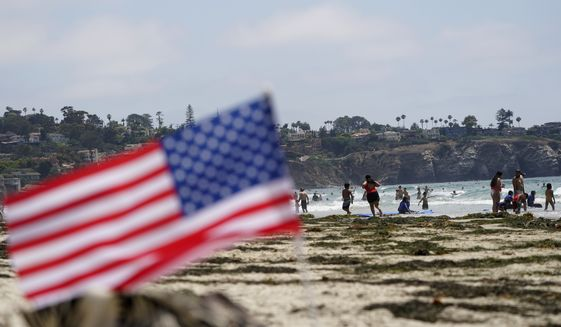 People walk along La Jolla Shores beach as Independence Day weekend nears, Thursday, July 1, 2021, in San Diego. Holiday travel over the Independence Day weekend is expected to nearly return to pre-pandemic levels, according to AAA. (AP Photo/Gregory Bull)