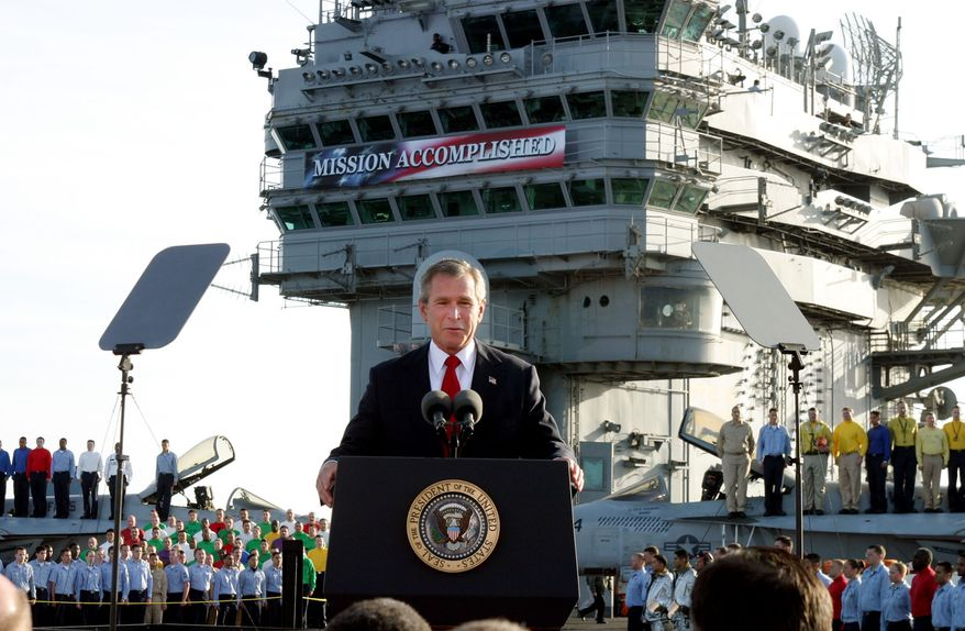 In this file photo, President Bush declares the end of major combat in Iraq as he speaks aboard the aircraft carrier USS Abraham Lincoln off the California coast, in this May 1, 2003 file photo.  More than 18 years later, the legislation authorizing the Persian Gulf War and the Iraq War remain on the books. The Senate Foreign Relations Committee met on August 3, 2021, to grapple with a measure to repeal the 1991 and 2002 Authorizations for the Use of Military Force (AUMF), which provided the legal justification for the Gulf War and the 2003 invasion of Iraq.   (AP Photo/J. Scott Applewhite, File)