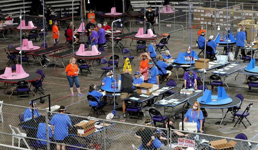 In this May 6, 2021, file photo, Maricopa County ballots cast in the 2020 general election are examined and recounted by contractors working for Florida-based company, Cyber Ninjas, at Veterans Memorial Coliseum in Phoenix. (AP Photo/Matt York, Pool, File)