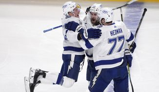 Tampa Bay Lightning's Jan Rutta (44) celebrates his goal against the Montreal Canadiens with Ondrej Palat (18) and Victor Hedman (77) during the first period of Game 3 of the NHL hockey Stanley Cup Final, Friday, July 2, 2021, in Montreal. (Paul Chiasson/The Canadian Press via AP)