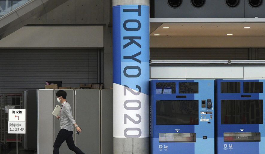 A man wearing a protective mask to help curb the spread of the coronavirus walks at pre-opened Main Press Center (MPC) for Tokyo 2020 Olympic Games at Tokyo Big Site Friday, July 2, 2021, in Tokyo. (AP Photo/Eugene Hoshiko) **FILE**