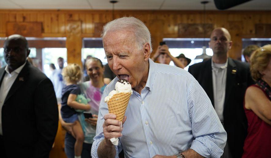 President Joe Biden eats ice cream as he visits Moomers Homemade Ice Cream, Saturday, July 3, 2021, in Traverse City, Mich. (AP Photo/Alex Brandon)