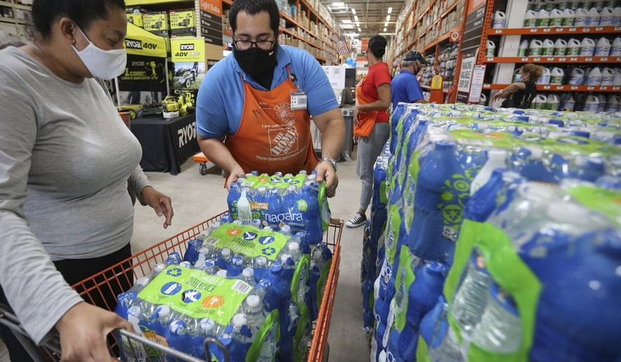 Home Depot department supervisor, Arnaldo Gonzalez, loads water bottles into Elena Arvalo's shopping cart as shoppers prepare for possible effects of tropical storm Elsa in Miami on Saturday, July 3, 2021. Elsa fell back to tropical storm force as it brushed past Haiti and the Dominican Republic on Saturday and threatened to unleash flooding and landslides before taking aim at Cuba and Florida.  (Al Diaz/Miami Herald via AP)
